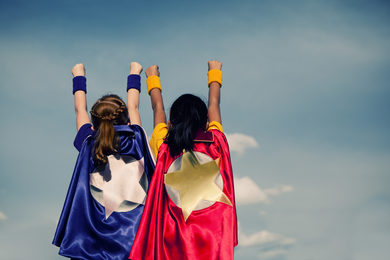 Two girls pose in superhero costumes.