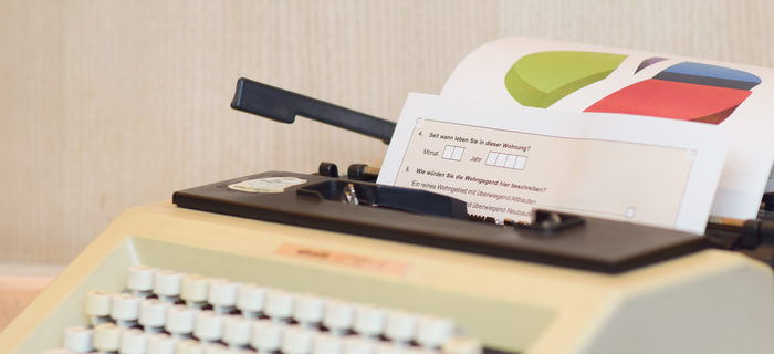 typewriter with a chart and a questionnaire